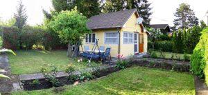 Kleingarten Hütte aus den sechziger Jahren mit Wiese und Blumenbeeten